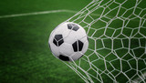 Soccer ball on goal with net and green background