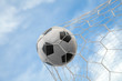 Soccer ball on goal with net and sky background