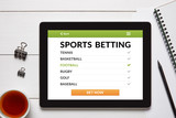 Sports betting concept on tablet screen with office objects on white wooden table. All screen content is designed by me. Flat lay