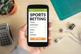 Hand holding smart phone with sports betting concept on screen. All screen content is designed by me. Flat lay