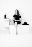 black and white retro portrait of woman with bottle wine, dress, legs, hat - 198319865