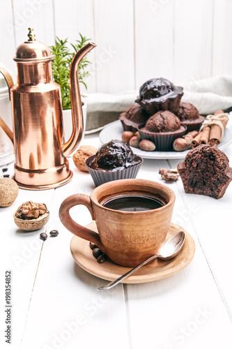 Kawa w glinianej filiżance z czekoladowym słodka bułeczka na białej drewnianej desce
