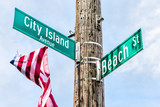 City Island Avenue and Beach street signs at intersection in Bronx, New York City, NYC with american flag - 198356489