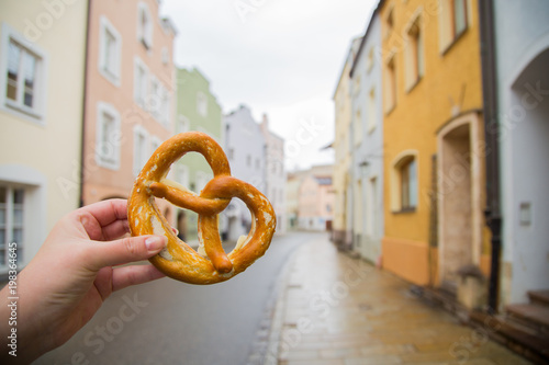 Pretzel with butter in hand of tourist in Germany. Historical Bavarian town of Burghausen street of coloured houses and traditional piquant or sweet pastry.
