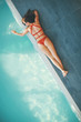 Young woman lying by swimming pool
