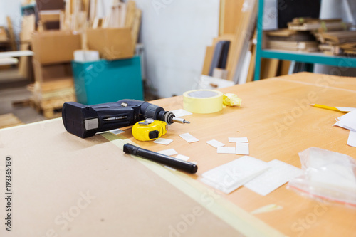 production, manufacture and woodworking industry concept - screwdriver and ruler on table at workshop