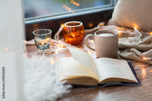 Fotobehang Chocolade hygge and cozy home concept - book, cup of coffee or hot cchocolate and candles with garland on window sill