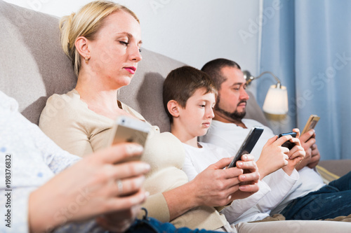 Modern family with smartphones at home