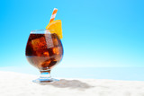 Refreshing Cola with ice and a slice of orange in a glass on the sandy coast