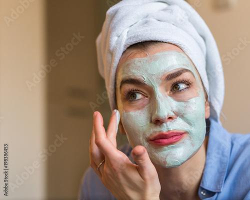 Foto Murales Woman applying cosmetic face mask