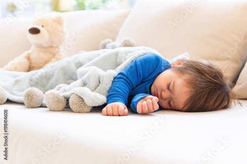 Sleepy toddler boy napping in the afternoon on a sofa