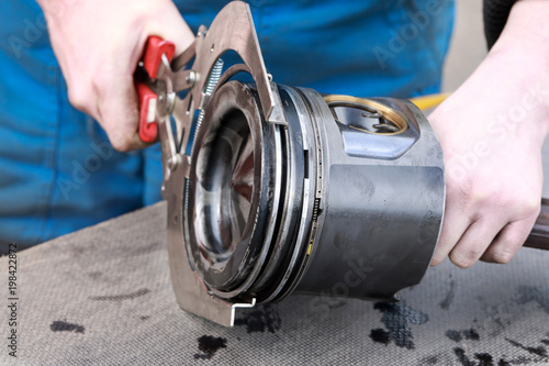 The mechanic puts rings on the piston from the truck's engine with a special tool. Close-up.