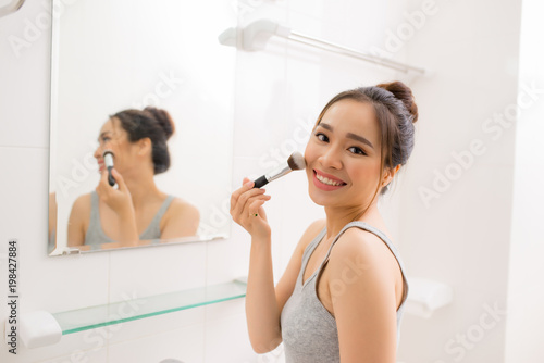 Beautiful woman applying makeup blusher in her bathroom