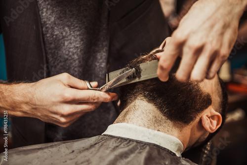 Professional Master hairdresser cuts client beard.