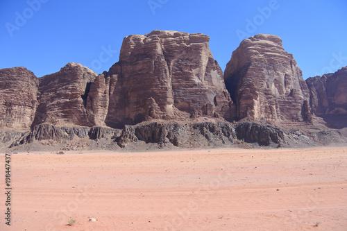 Fahrspuren im Sand vor Felstürmen im Sand im Wadi Rum in Jordanien Poster