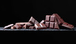 Broken chocolate pieces on a black background.
