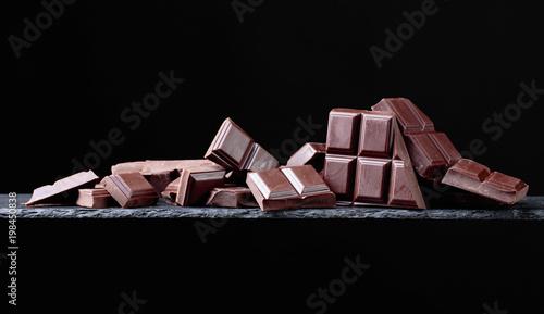 Łamani czekoladowi kawałki na czarnym tle.