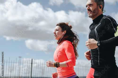young adults couple running together - 198464295