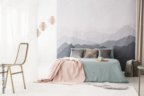 Cozy bed by landscape wallpaper