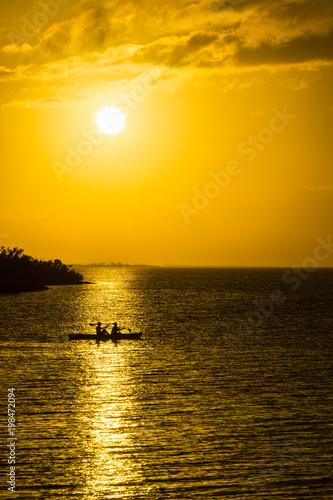 Fotobehang Meloen USA, Florida, Warm orange evening sunlight reflection with canoe on ocean water