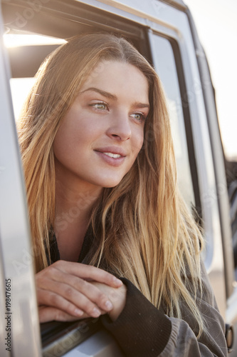 Young white woman looking away through open window of a car