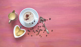 Cup of cappuccino coffee, sugar, milk and coffee beans on red table, free copy space