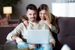 Beautiful young smiling couple using their laptop at home.
