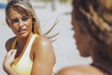 Young beautiful blond woman in sportswear sitting in windy on shoreline and chatting with anonymous friend.
