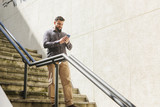 bearded man looking amartphone while walking down the stairs - 198498885