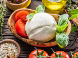Buffalo mozzarella in the wooden bowl on the table. Food background.