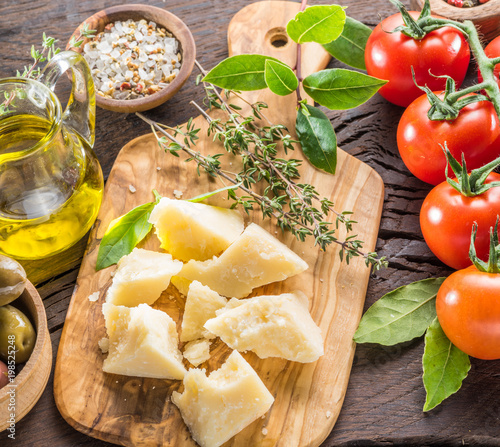 Parmesan cheese on wooden cutting board. Food background. - 198525248