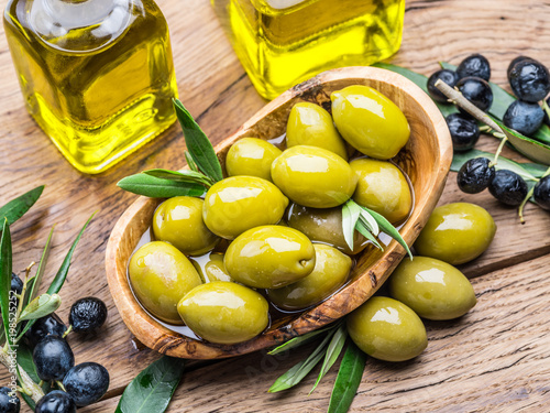 Olive berries and bottle of olive oil on the wooden table. - 198525252