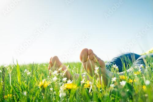 Fotobehang Gras bare feet on spring grass and flowers