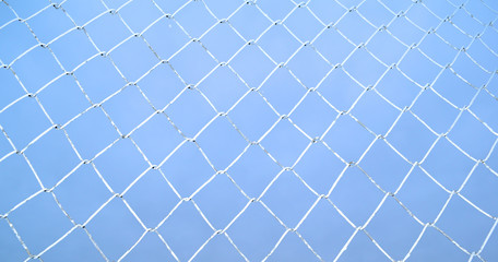 The view through the background of metal mesh on the sky is overcast.