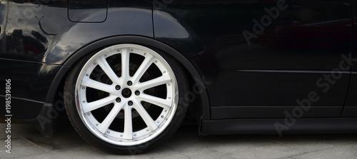 Widok z boku na czarny błyszczący samochód z białymi kołami