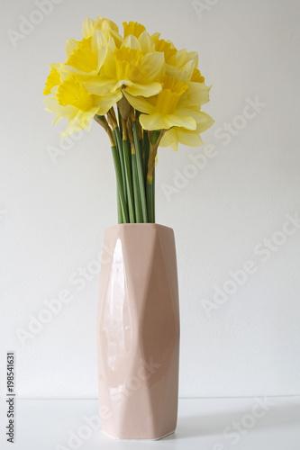 bukiet żółtych żonkili w różowym wazonie