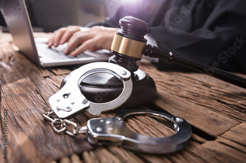 Close-up Of Handcuffs And Gavel In Courtroom