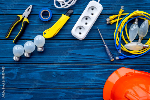 Electrician work concept. Hard hat, tools, cabel, bulb, socket outlet on blue wooden background top view copy space