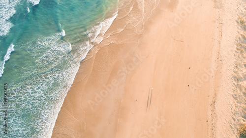 Foto Murales Aerial View of People Walking Along Beach at Sunset