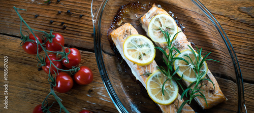 Poster Graffiti Salmon. Two juicy salmon steaks in roast pan with herb decoration on rustic oak table.