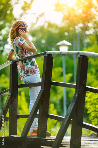 Cheerful girl using cellphone on a nice summer day.