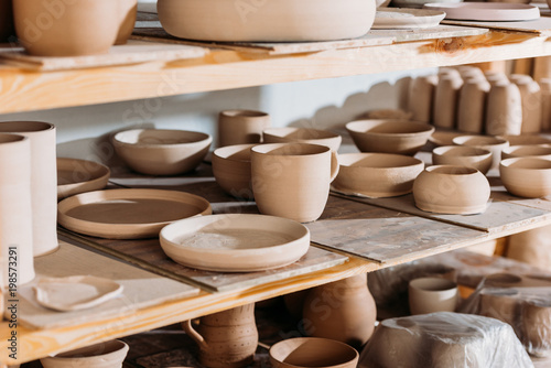 ceramic plates and bowls on wooden shelves in pottery workshop
