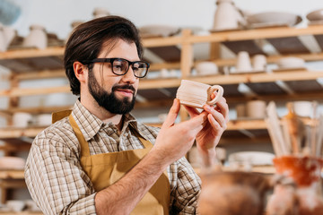 male potter in apron looking at little ceramic cup