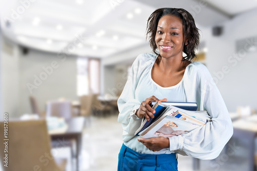 Young african woman holding pile of magazines