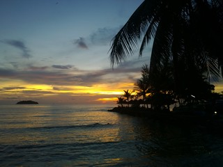 Sunset glow over a beautiful tropical beach and ocean water. Different colours of clouds and the silhouette of palm tree.  Rich deep vivid colors of oranges, reds, blues & yellows. Koh Chang Thailand