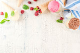 Summer sweet berries and desserts, various of ice cream flavor in cones pink (raspberry), vanilla and chocolate with mint on light concrete background copy space