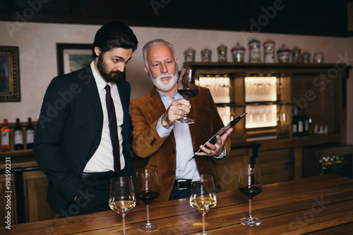 Winemakers in wine cellar holding glass of red wine and checking it. Sommeliers testing wines in winery.  © hedgehog94