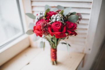 wedding bouquet of red flowers and greenery stands near the window
