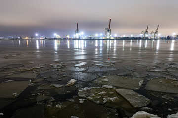 Night photography long exposure. Riga, Latvia industrial port details over frozen river