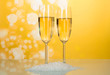 Two wonderful wineglass of champagne with bubbles of air, near handful of artificial snow on bright yellow